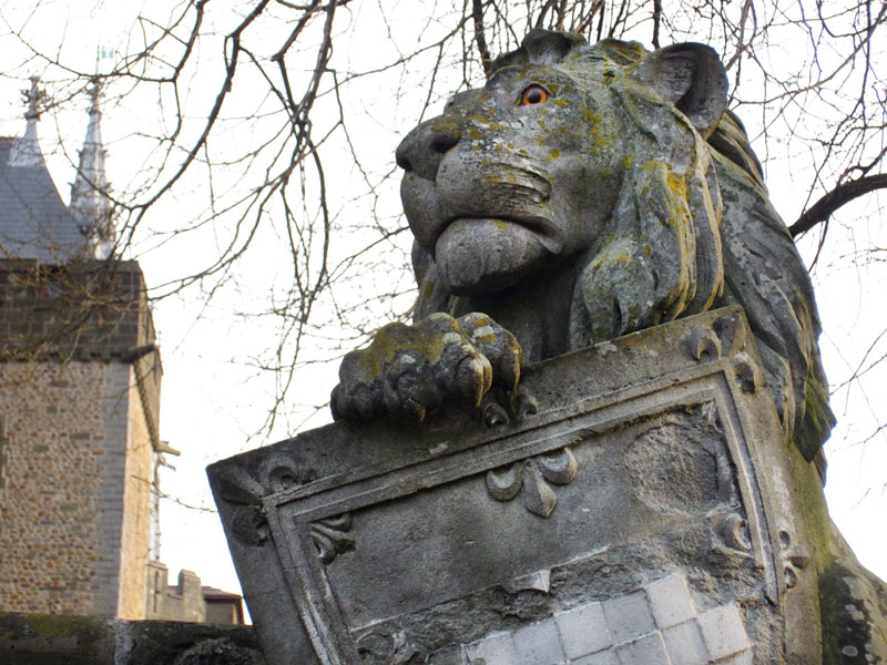 statue depicting a lion and an escutcheon. in the background one can see parts of a castle complex