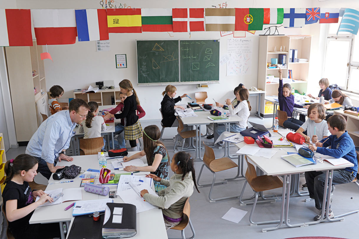 picture of a lesson in an elementary school classroom. The tables are arranged so that the students can work in small groups. The teacher is standing next to one group and is explaining something.