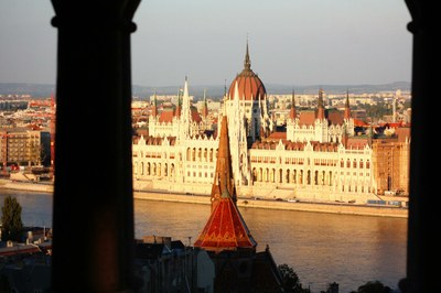 photograph from the other side of the Danube of the parliament building in Budapest, the sun is setting and illuminates the building