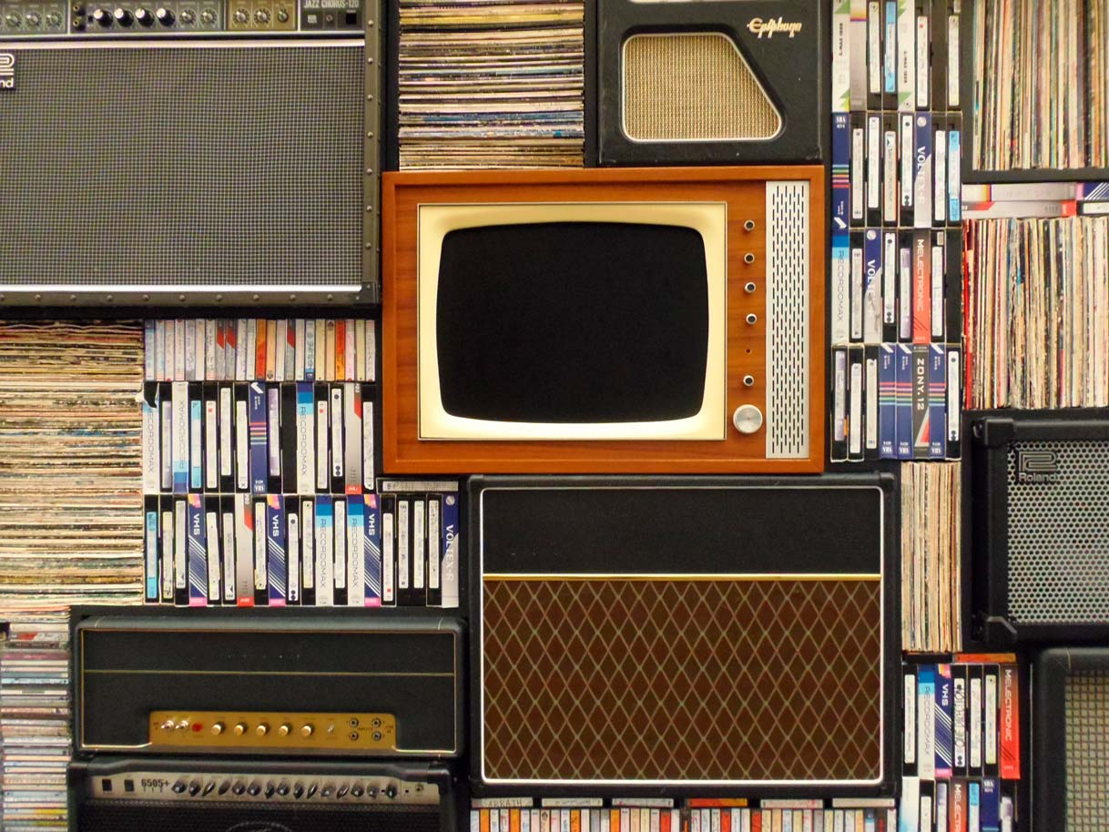 front view of a shelving unit containing a myriad of records, MCs, and video cassettes, as well as a historical television and several guitar amplifiers