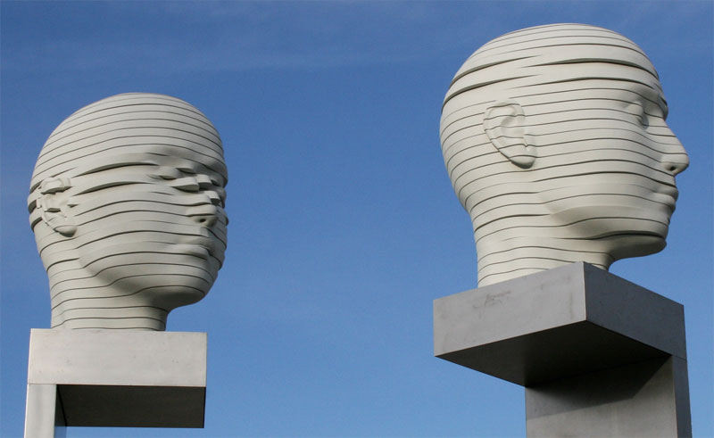 sculpture of two heads against the backdrop of a clear sky. The heads seem to be cut into horizontal slices, some of which are slightly moved out of place