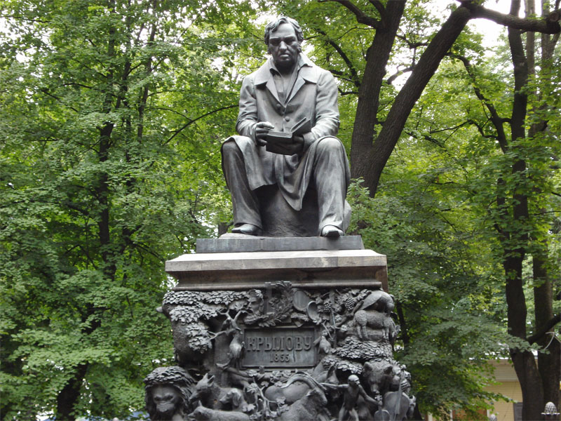 monument of a sitting man holding an opened book it his hand, in the background a green forest