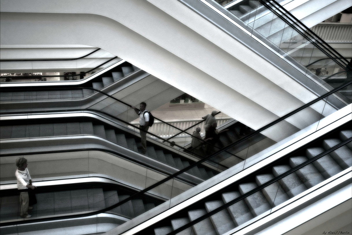 photograph depicting several moving staircases in a mall