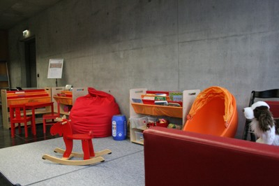 View into the parent-child area with rocking elk, play shelf, beanbag, tables and sofa