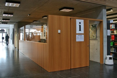 The information desk in the Science Branch Library. It is separated from by a wooden wall and an area of glass. The door ist open.