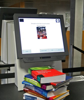 Photo of the self loan machine, with a stack of books on top