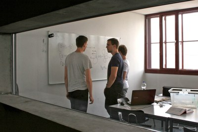 View into the group room, three people stand at the whiteboard and consult each other.