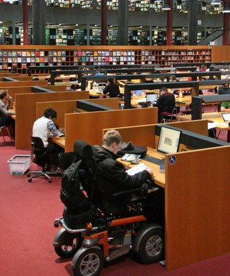 A man in a electric wheelchair working at a height-adjustable computer workstation in the reading room