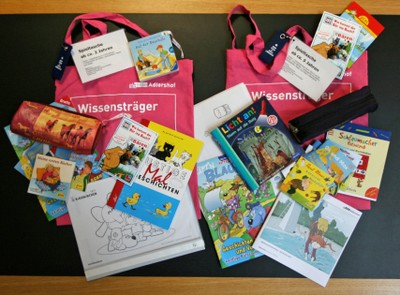 The content of both play bags: books, colouring templates and pencils